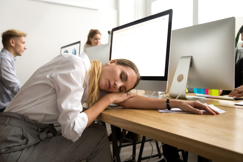 Restless young businesswoman sleeping at work desk, tired or bored female employee lying asleep at workplace at break, exhausted overworked office worker feeling lack of sleep or fatigue having nap