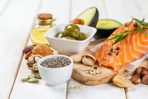 Selection of healthy unsaturated fats, omega 3 - fish, avocado, olives, nuts and seeds