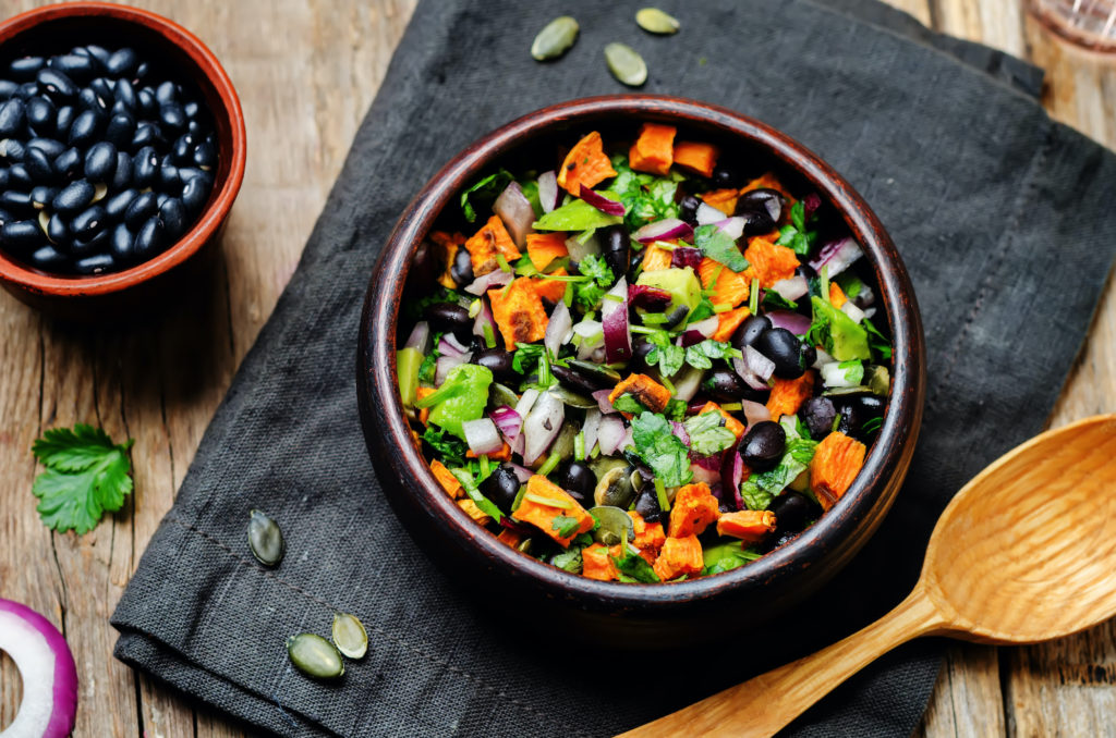 Roasted sweet potato black bean pepita avocado salad. toning. selective focus