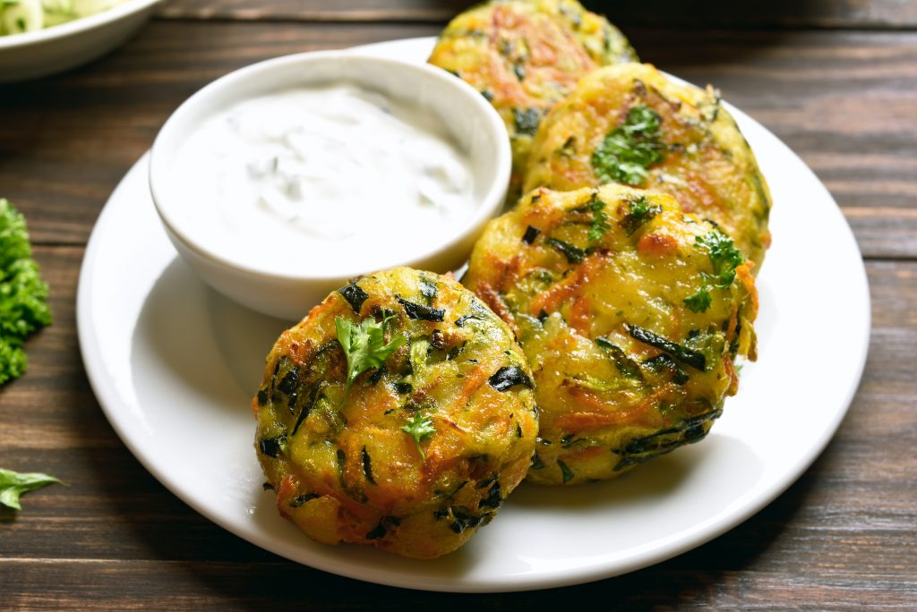 Tasty vegetable cutlet from carrot, zucchini, potato with sauce. Healthy diet food. Close up view