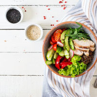 Buddha bowl dish with chicken fillet, quinoa, avocado, sweet pepper, tomato, cucumber, radish, fresh lettuce salad and sesame. Detox and healthy superfoods bowl concept. Overhead, top view, flat lay.