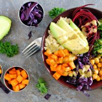 Buddha bowl with quinoa, avocado, chickpeas, vegetables on a dark stone background, Healthy eating concept. Overhead scene.