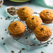 Pumpkin whole wheat muffins for breakfast on turquoise background